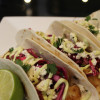 Beer Battered Fish Tacos with Cilantro Lime Red Cabbage Slaw, Avocado Crema, and Cotija Cheese
