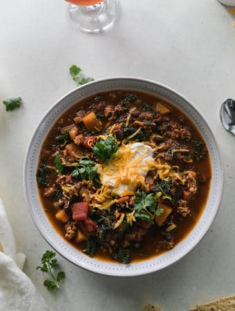 Overhead shot of a bowl of chili topped with sour cream, shredded cheddar, and cilantro