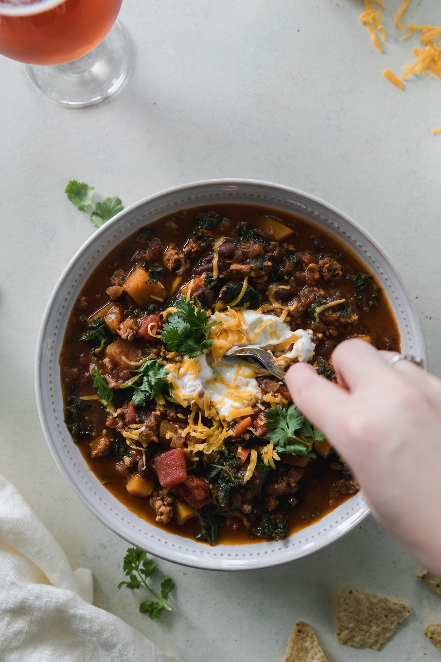 Overhead shot of a bowl of chili topped with sour cream, shredded cheddar, and cilantro, with a hand stirring the chili with a spoon