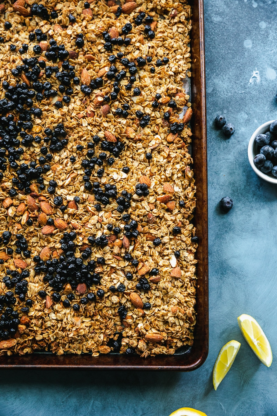 Overhead shot of a baking sheet filled with lemon blueberry granola against a blue background