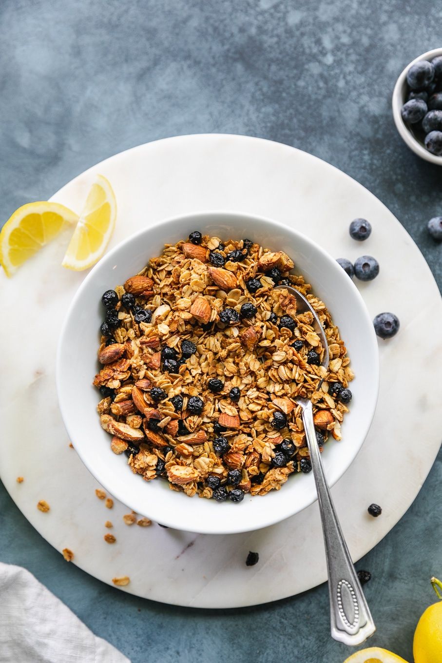 Overhead shot of a bowl of lemon blueberry granola with a spoon in the bowl
