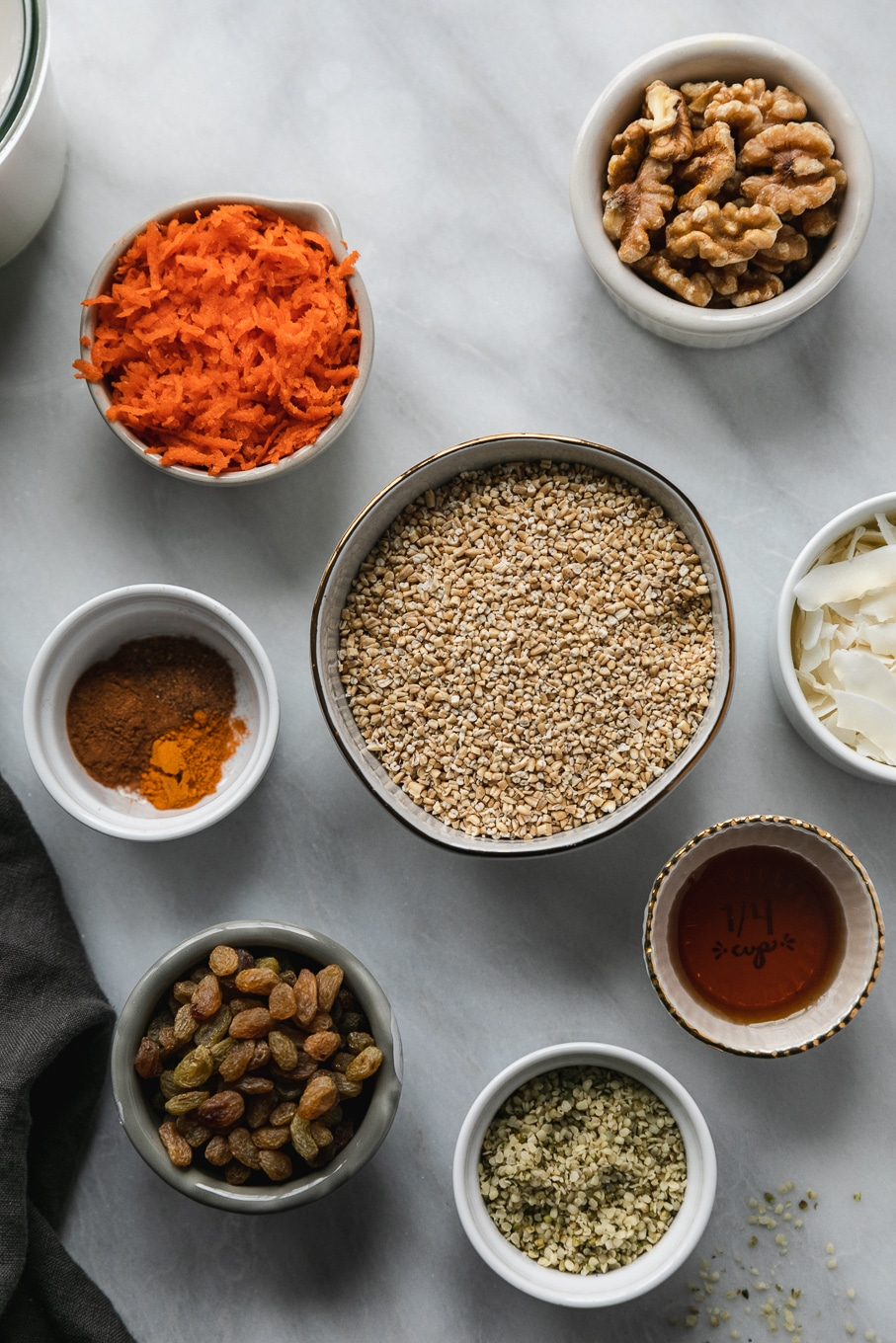 Overhead shot of a bowl of steel cut oats surrounded by ramekins of grated carrots, spices, golden raisins, hemp seeds, maple syrup, coconut flakes, and walnuts