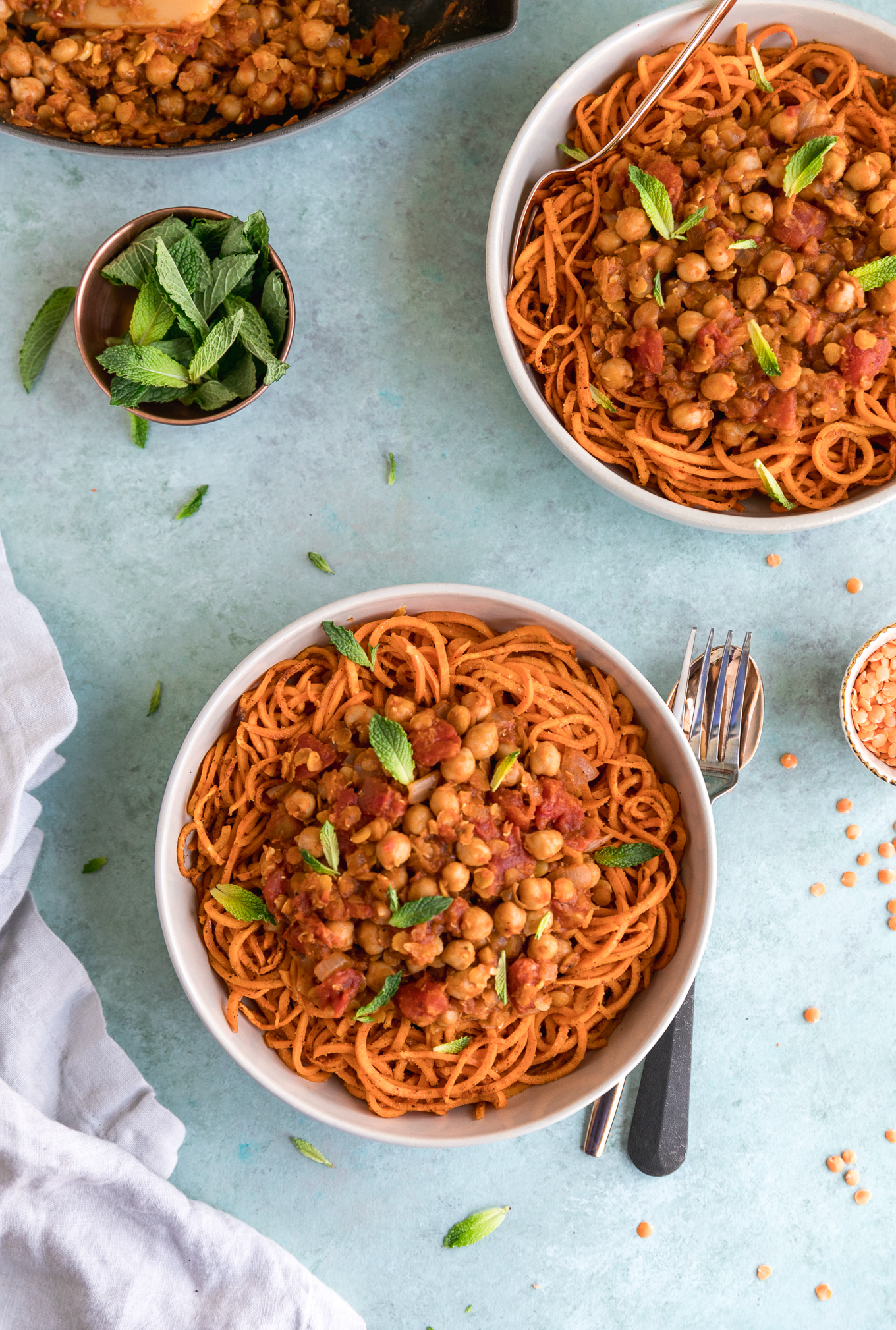 Overhead shot of two bowls of sweet potato noodles with a small bowl of mint leaves and dry lentils, and a fork and spoon stacked on top of each other