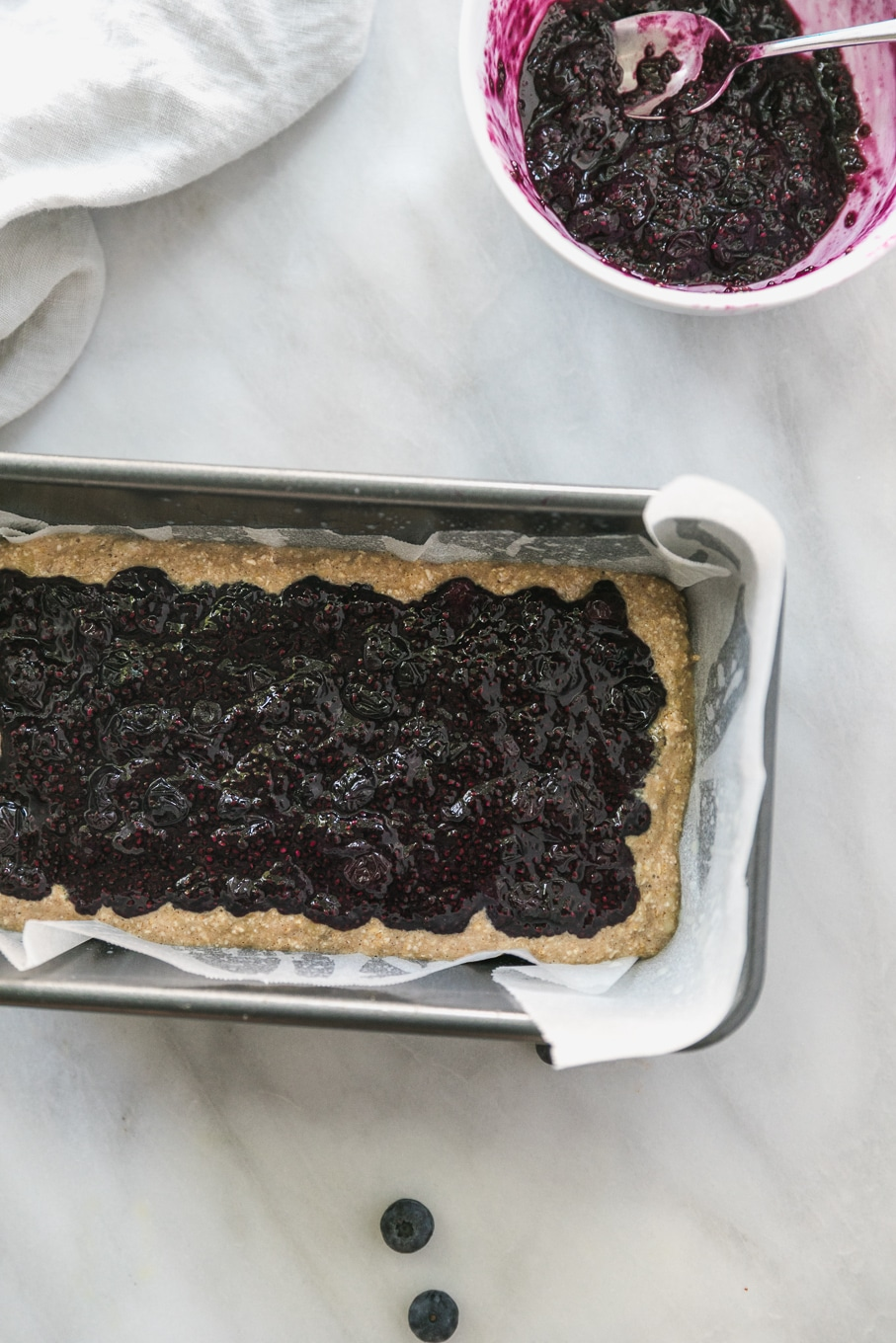 Overhead shot of a loaf pan filled with banana bread batter and a layer of blueberry chia jam