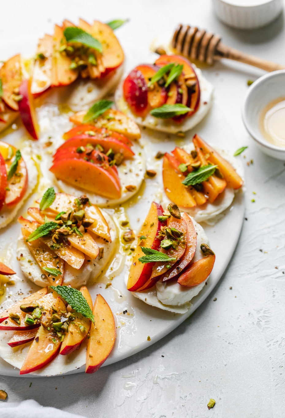 Close up shot of peach caprese with pistachios and mint