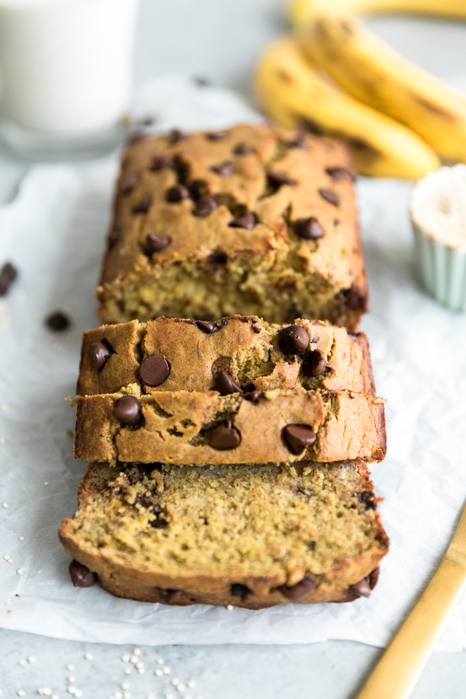 Forward facing shot of a loaf of chocolate chip banana bread with a few slices cut laying on each other