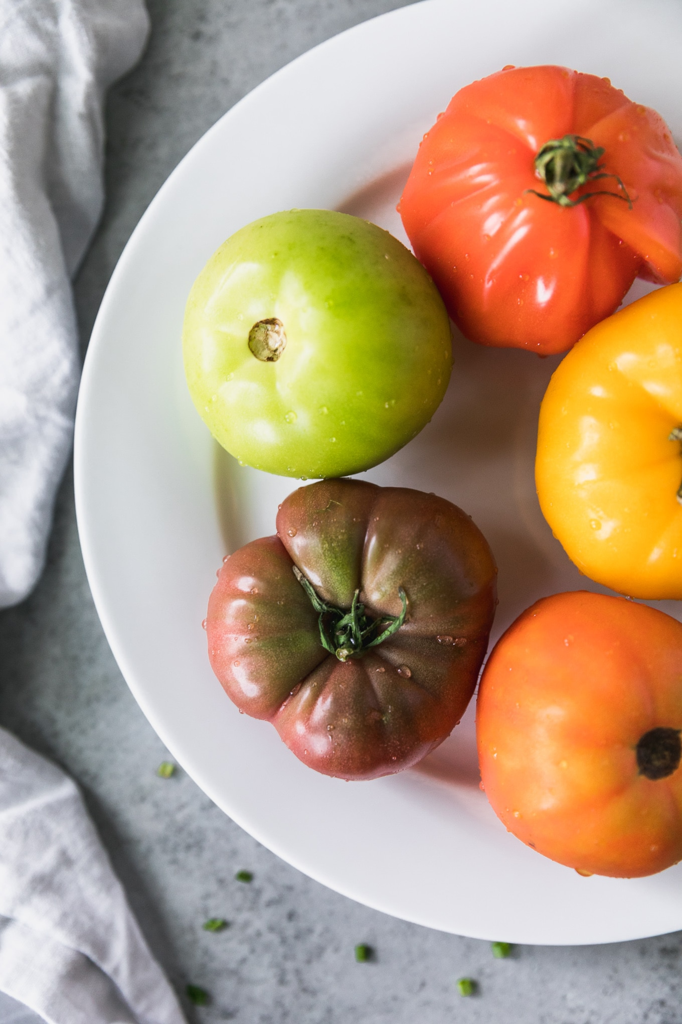 Overhead close up shot of a white plate with all different brightly colored heirloom tomatoes on it