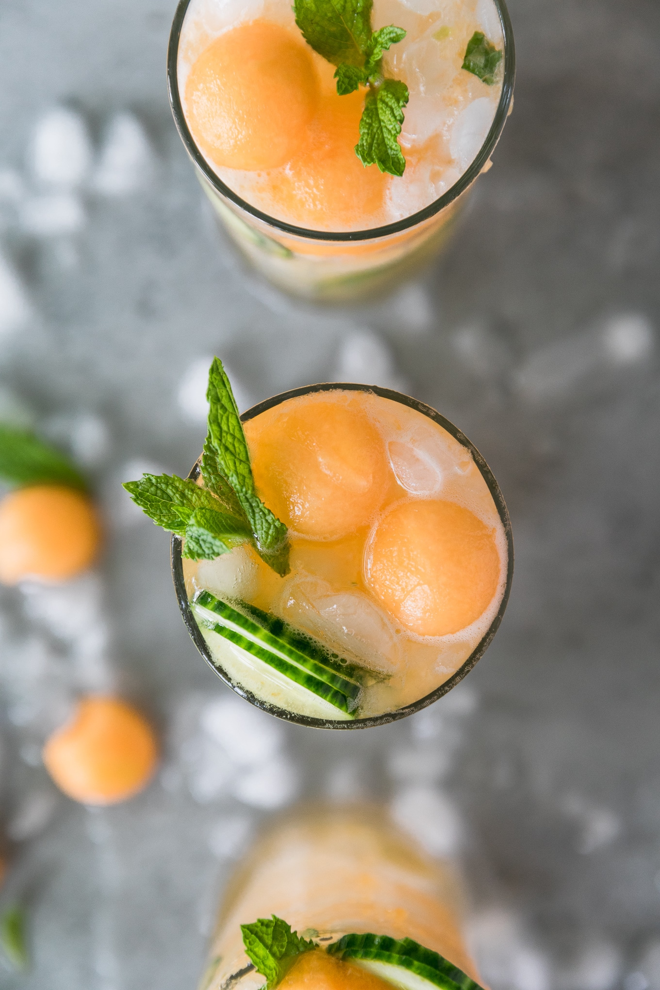 Overhead shot of three cocktails topped with melon balls, sliced cucumber, and a spring of mint