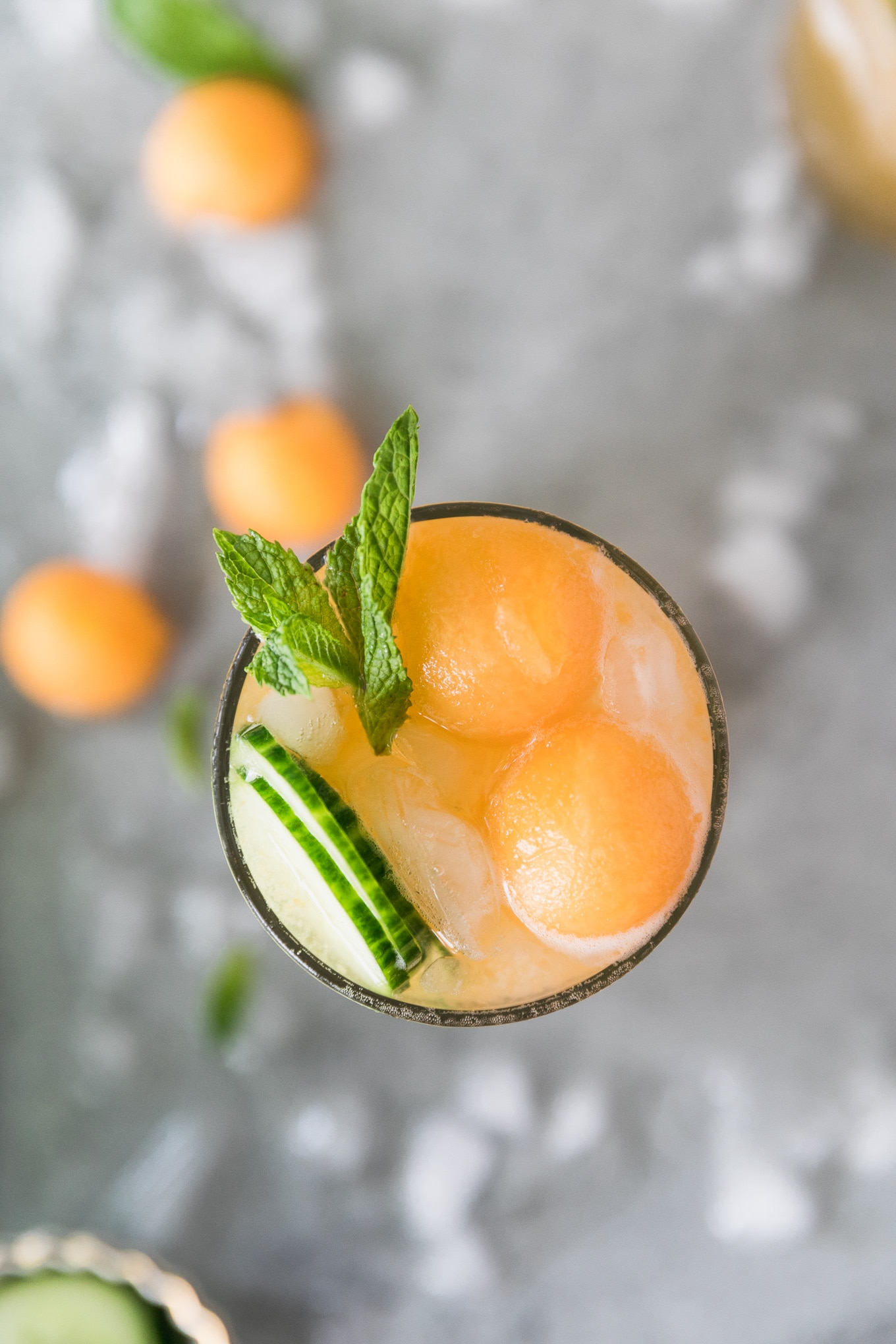 Overhead close up shot of a cocktail topped with melon balls, sliced cucumber, and a spring of mint