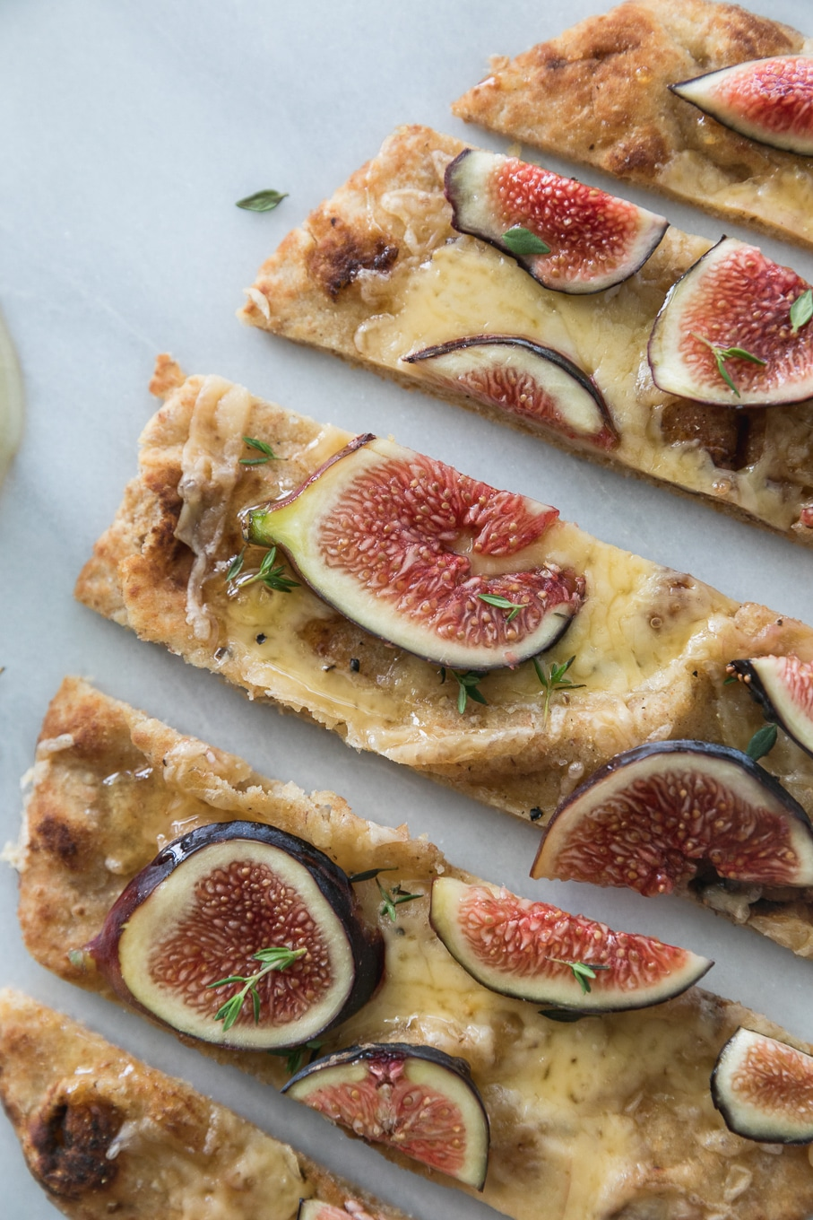 Overhead close up shot of a fig flatbread sliced into pieces