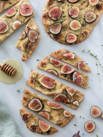 Overhead shot of 3 fig flatbreads sliced into pieces with thyme sprigs and a honey dipper alongside them