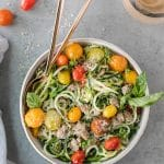 Overhead shot of zucchini noodles with roasted colorful baby heirloom tomatoes, fresh basil, and chicken sausage, with a gold fork and spoon resting in the bowl pointing out from the left, and a glass of rosé on the side