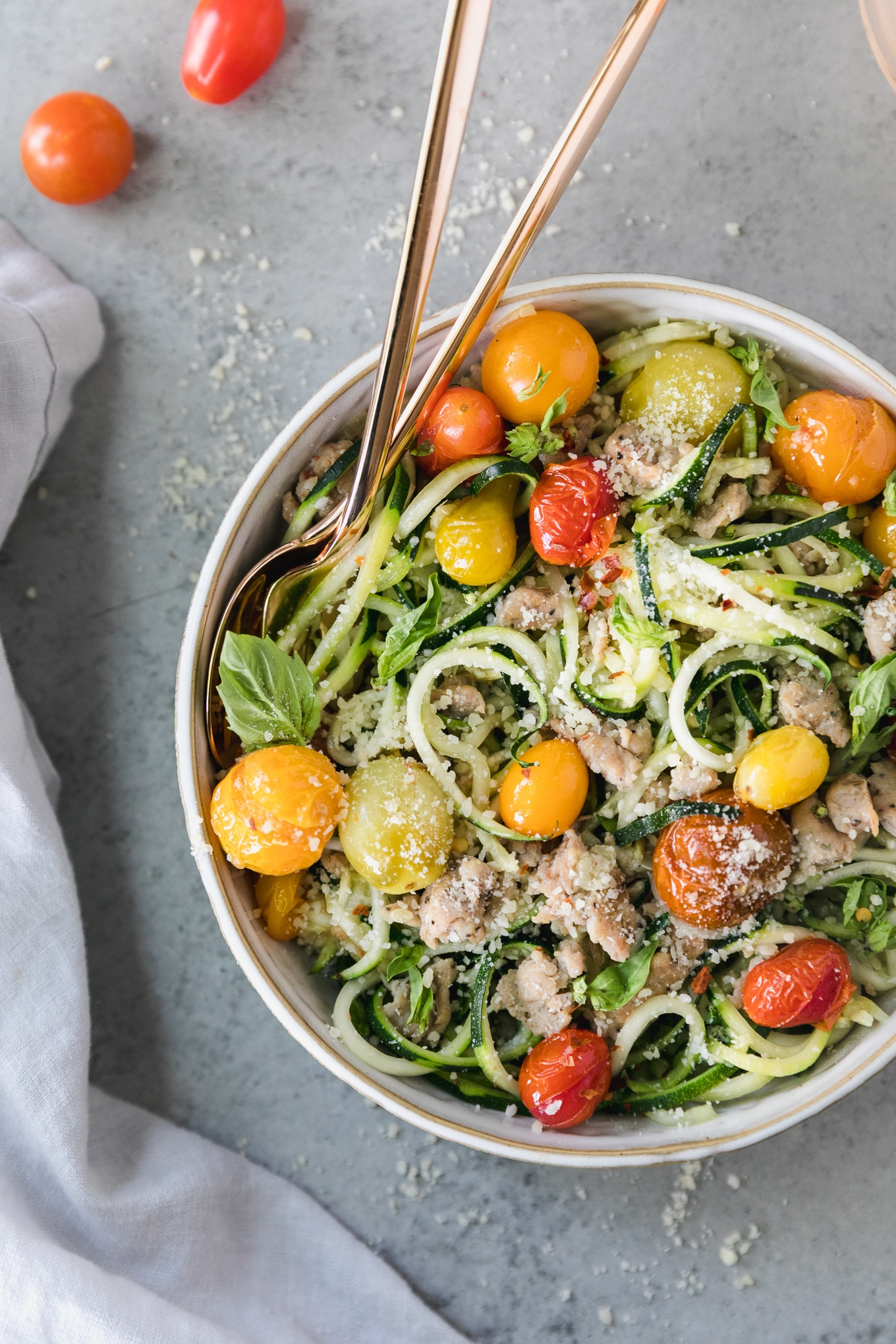 Overhead shot of zucchini noodles with roasted colorful baby heirloom tomatoes, fresh basil, and chicken sausage, with a gold fork and spoon resting in the bowl and a bluish grey napkin on the left side