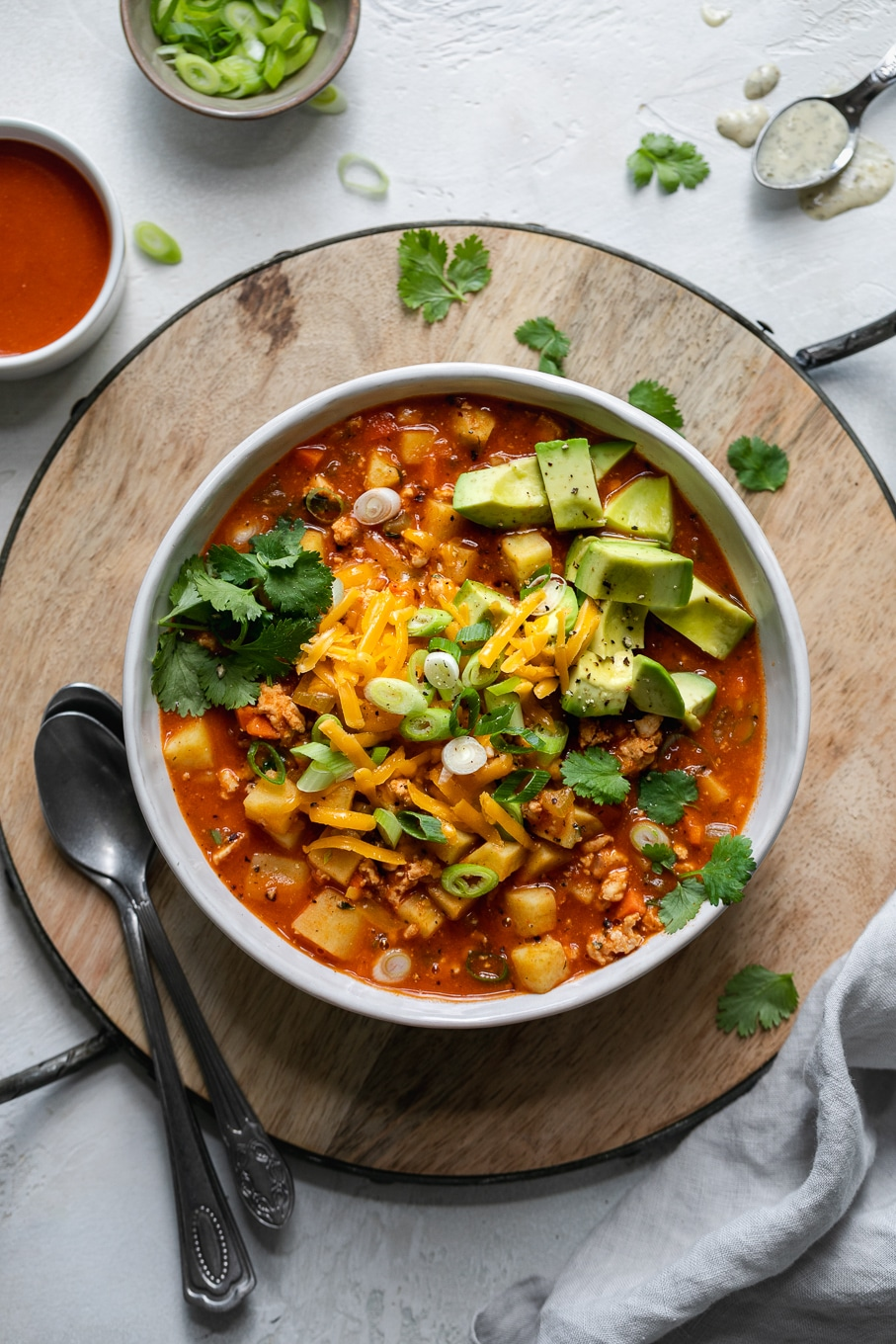 Overhead shot of a bowl of buffalo chicken chili topped with cheese, cilantro, and avocado