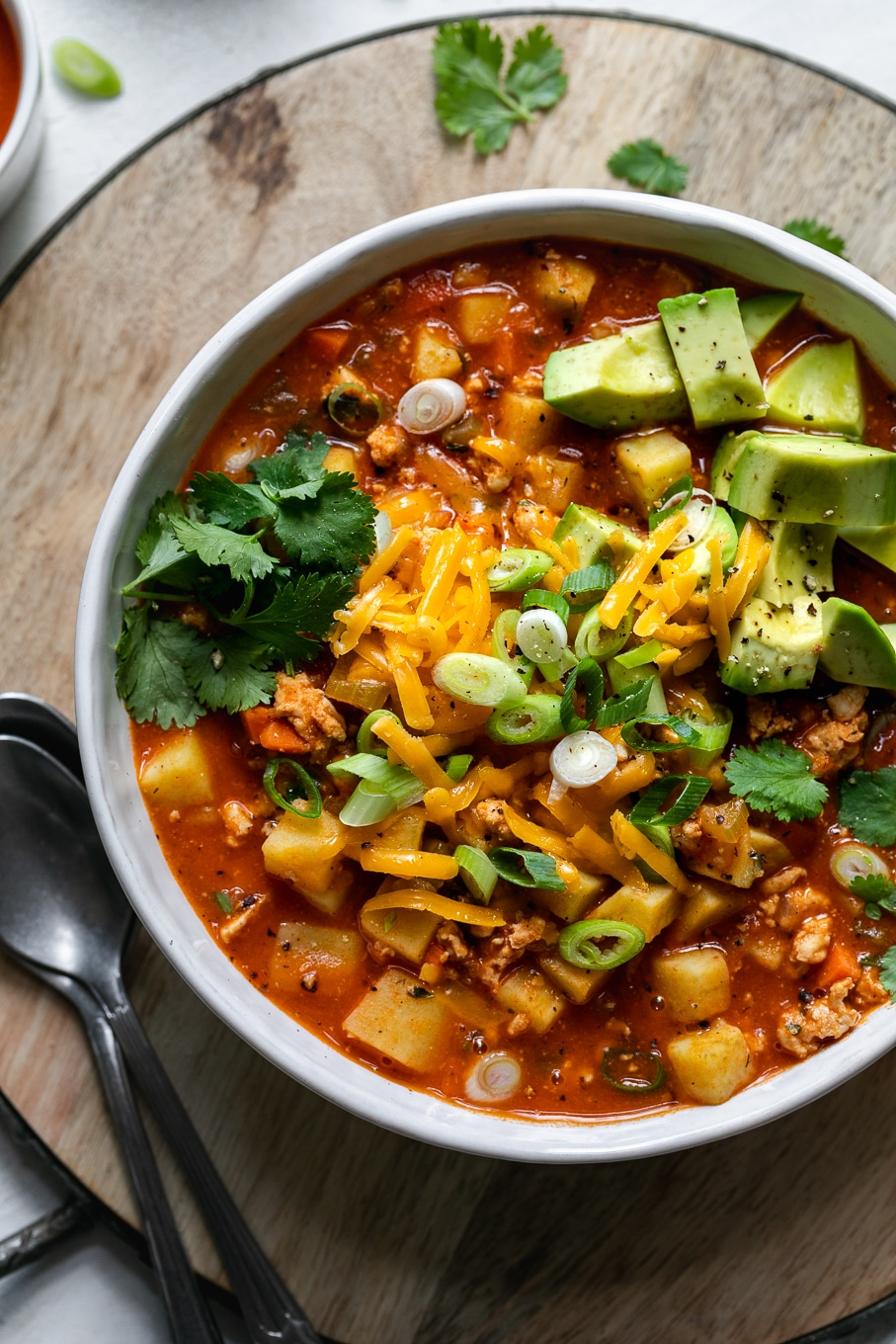 Overhead close up shot of a bowl of buffalo chicken chili topped with cheese, cilantro, and avocado