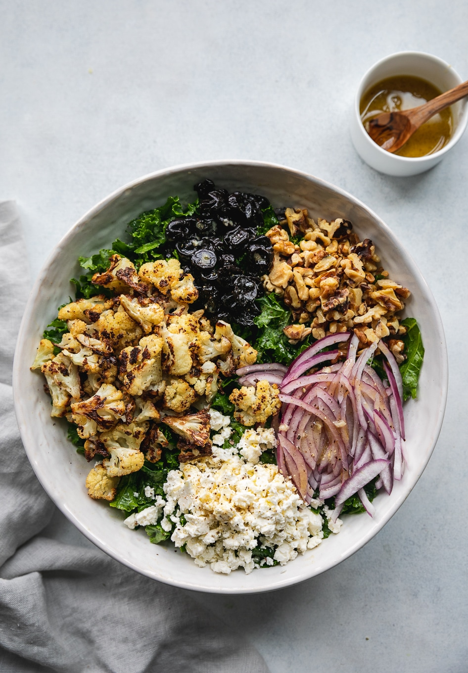 Overhead shot of a bowl of kale salad topped with piles of roasted cauliflower, dried cherries, toasted walnuts, red onion, and feta