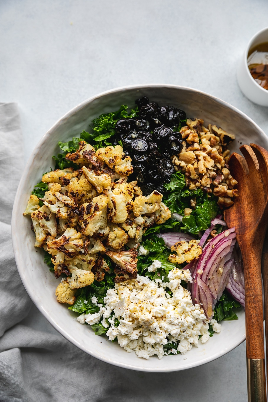 Overhead close up shot of a bowl of kale salad topped with piles of roasted cauliflower, dried cherries, toasted walnuts, red onion, and feta, with a wooden salad server in the bowl