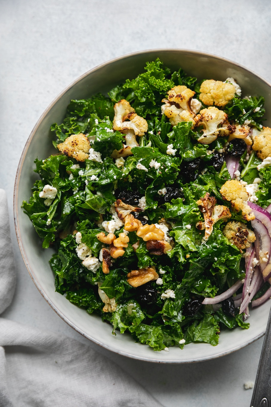 Overhead close up shot of a bowl of kale salad with roasted cauliflower, red onion, feta, dried cherries, and walnuts
