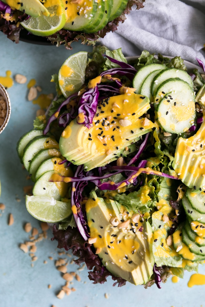 Overhead closeup shot of a salad topped with sliced avocado and cucumber, red cabbage, and sesame seeds