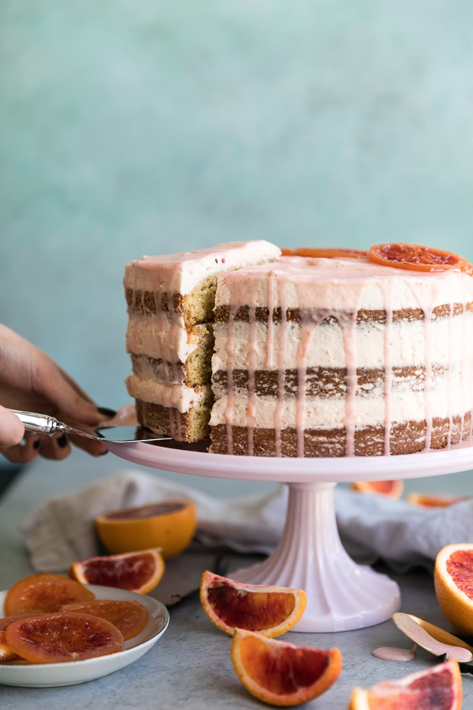 Forward facing shot of a blood orange layer cake with pink glaze dripping down and a slice being pulled out and blood orange wedges scattered around the below the cake stand