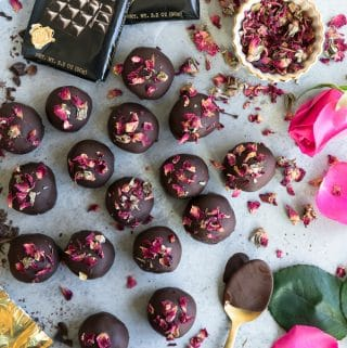 Overhead shot of chocolate covered truffles sprinkled with dried rosebuds with a small bowl of dried rosebuds and a fresh rose and a chocolate bar