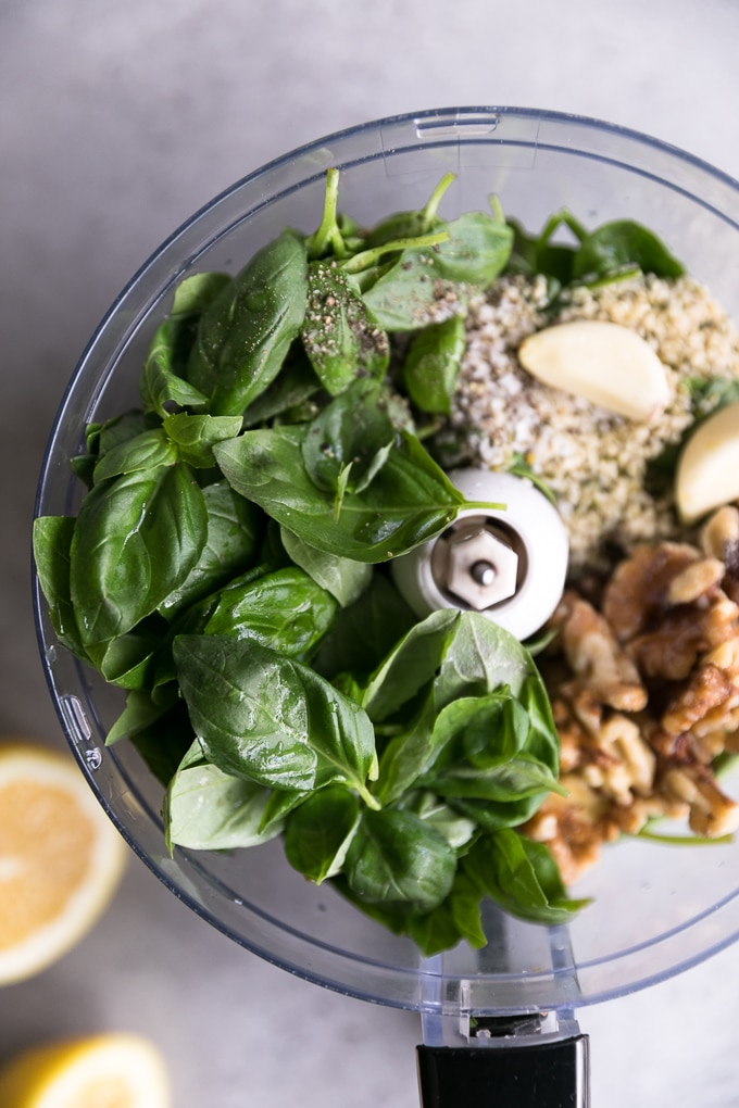 Close up shot of a food processor filled with basil, spinach, walnuts, garlic, and hemp seeds