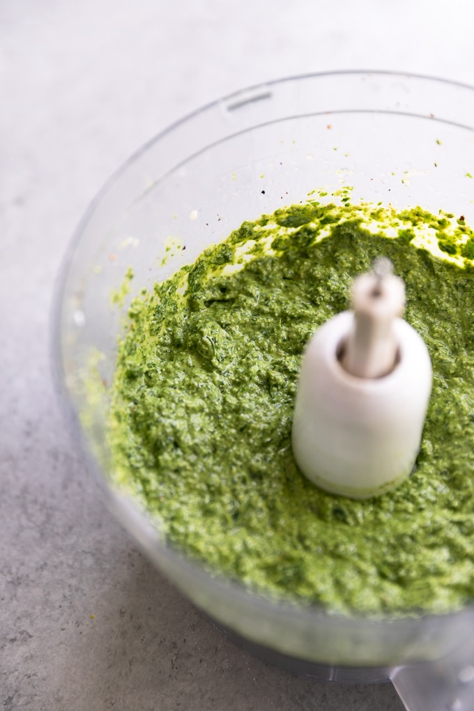 Close up shot of a food processor filled with pesto