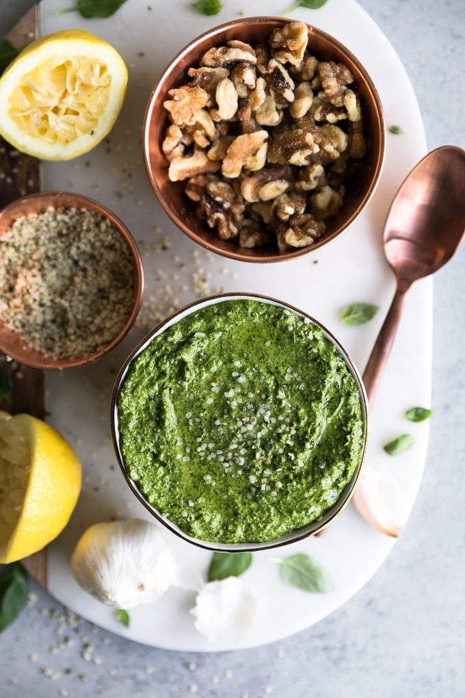 Overhead shot of a bowl of pesto with a bowl of walnuts above it, a bowl of hemp seeds, and a lemon and a bronze spoon beside it