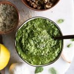 Overhead shot of a bowl of pesto with a spoon sticking out with a bowl of walnuts above it, a bowl of hemp seeds, and a lemon