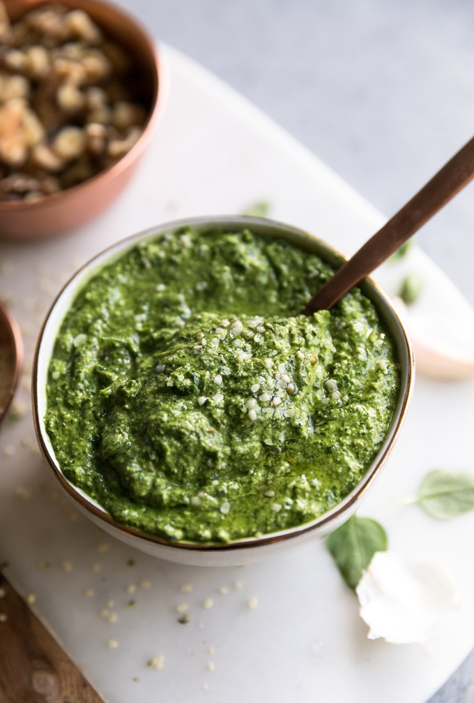 Close up shot of a bowl of pesto with a spoon sticking out and a blurred bowl of walnuts in the background