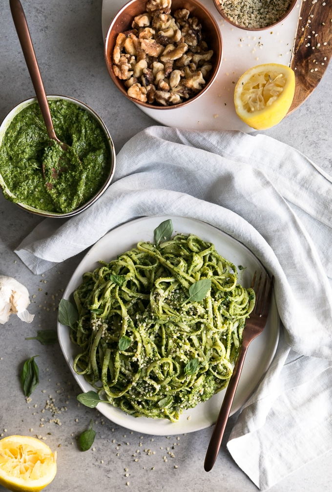 Overhead shot of a plate of pesto pasta with a bronze fork resting on the plate, with a bowl of pesto with a bronze spoon sticking out above it, as well as a bowl of walnuts and a squeezed lemon