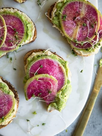 Overhead close-up shot of avocado toasts topped with watermelon radishes on a marble board with one bite taken out of one of the toasts