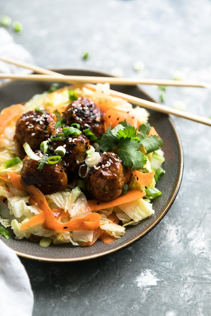 Close up shot of a plate of glazed meatballs over carrot and cabbage sauté garnished with cilantro, scallions, and white and black sesame seeds