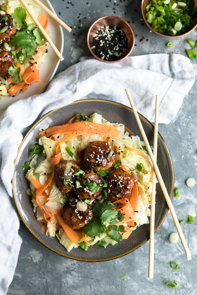 Overhead shot of glazed meatballs over napa cabbage and carrot ribbon sauté with chopsticks resting on the plate and sliced scallions scattered around