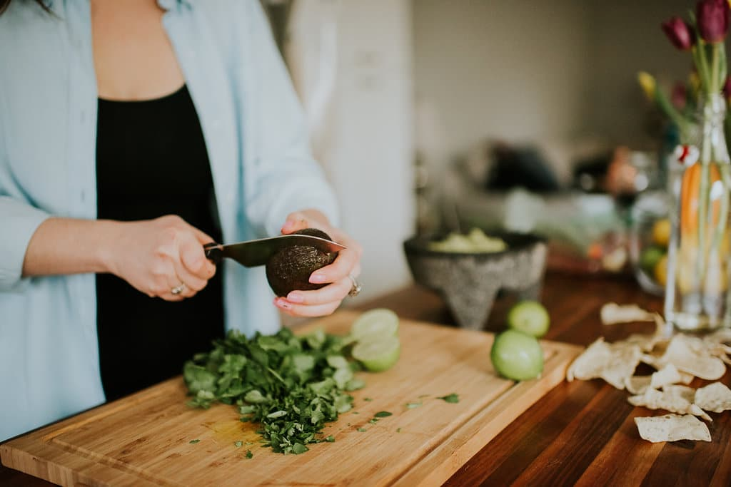 Neck down shot of a woman cutting an avocado in half with chopped cilantro and limes on the cutting board