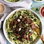 Overhead shot of a bowl of zucchini noodles topped with Korean beef, scallions, and sesame seeds with a gold fork sticking out on a light blue background
