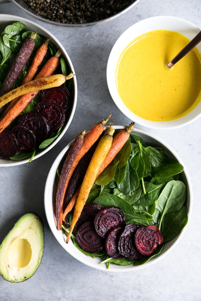 Overhead shot of two bowls of spinach topped with rainbow carrots and roasted beets, with a halved avocado and bowl of turmeric tahini dressing off to the side