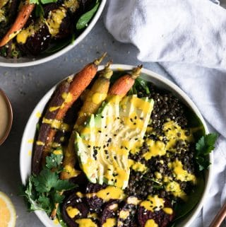 Overhead shot of a salad topped with lentils, roasted beets, rainbow carrots, parsley, sliced avocado, sesame seeds, and turmeric tahini dressing