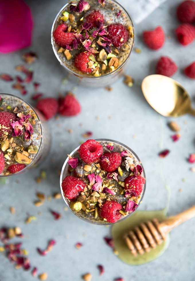 Overhead shot of three jars of chia pudding topped with raspberries, rosebuds, chopped pistachios, and honey, with a honey dipper and gold spoon in the background