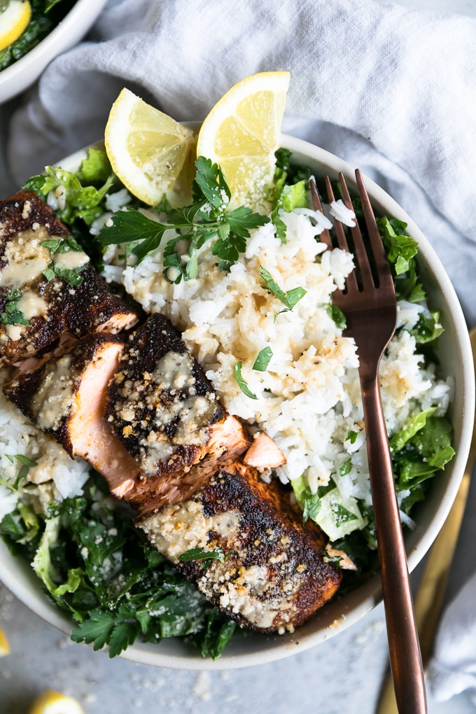 Overhead close up shot of a bowl of salad with rice, a salmon filet, and a fork resting on it and lemon wedges on the top