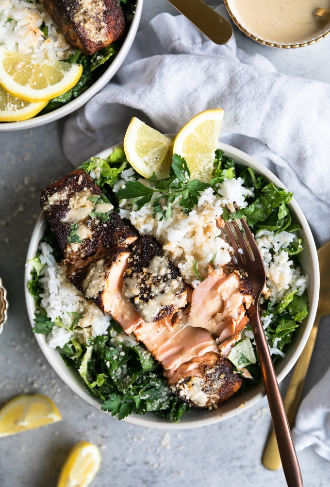Overhead shot of a bowl of salad with rice, a broken apart salmon filet, and a fork resting on it with lemon wedges on the top of the bowl