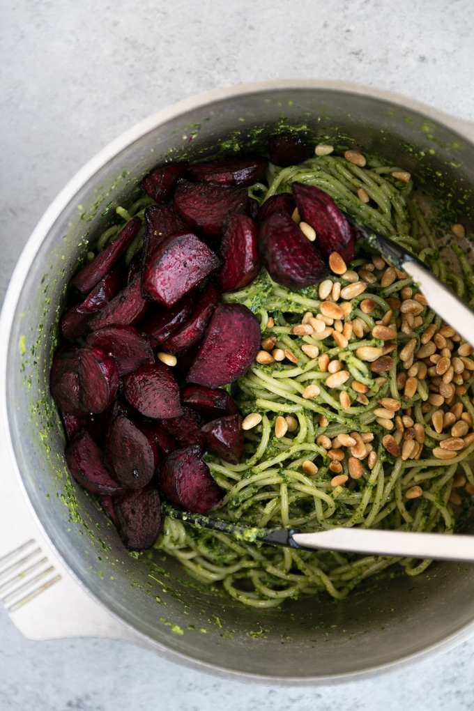 Overhead shot of a pot of pesto pasta with a pile of roasted beets on one side and toasted pine nuts on the other with a pair of tongs inside