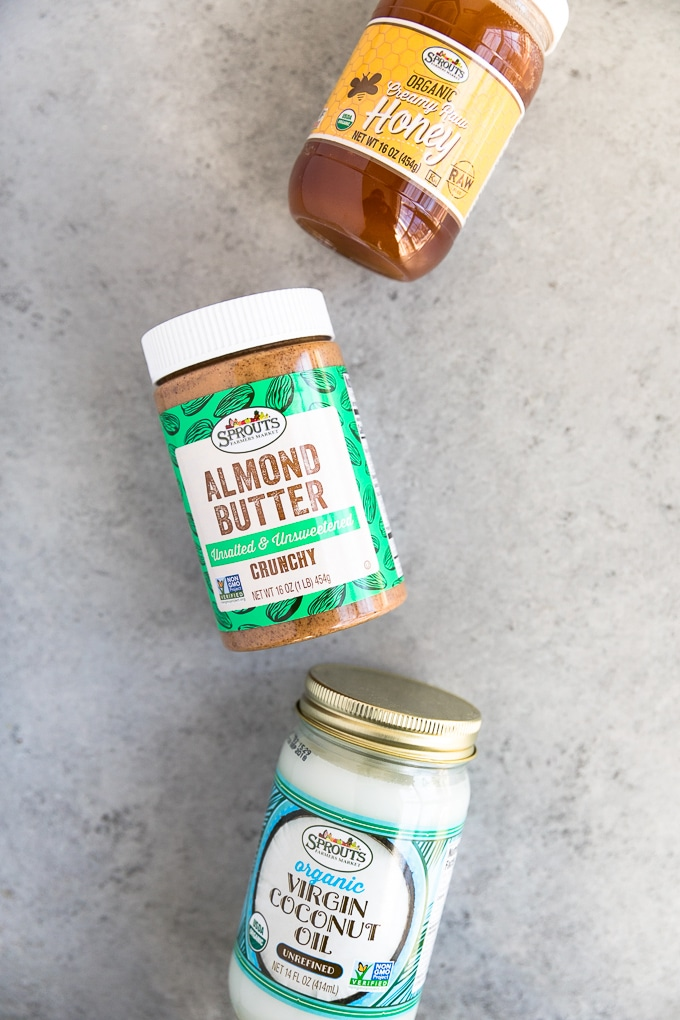 Overhead shot of a jar of honey, a jar of almond butter, and a jar of coconut oil