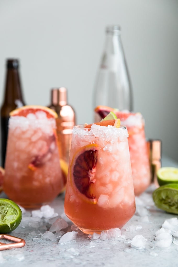 Straight on shot of three pink cocktails with a bronze shaker, beer bottle, and glass bottle in the background