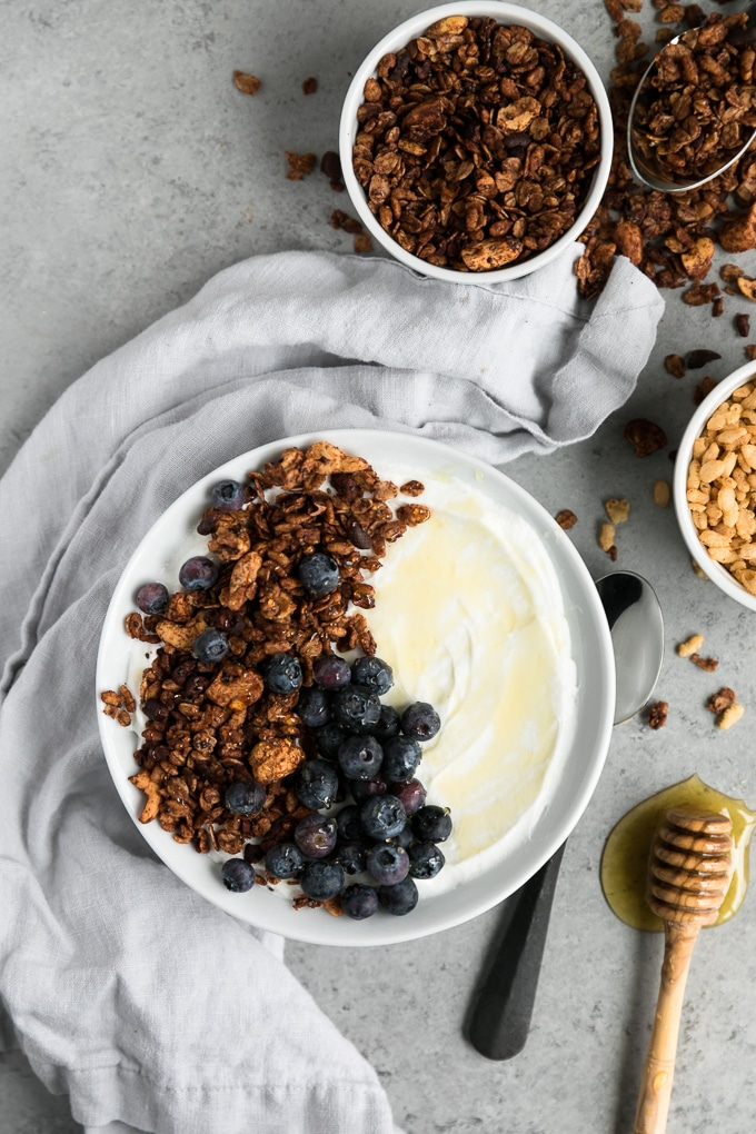 Overhead shot of a bowl of yogurt with granola, blueberries, and a napkin laid next to the bowl, as well as a bowl of puffed rice cereal and granola off to the side