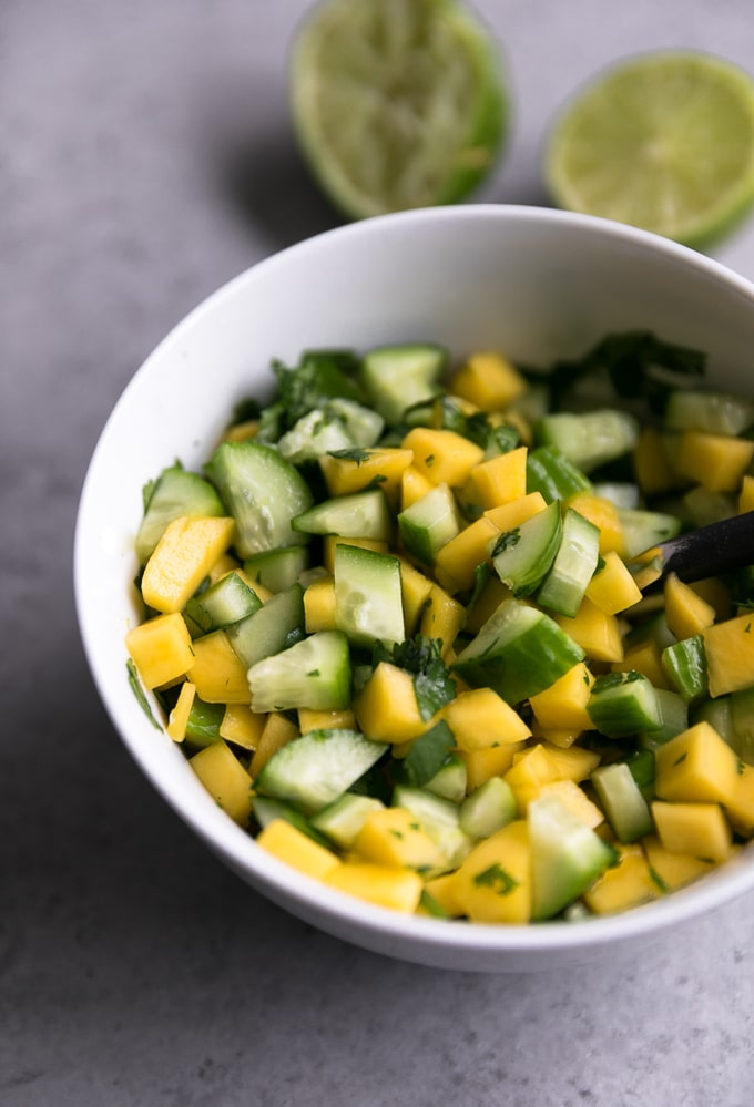 Close up shot of a bowl of mango cucumber salsa