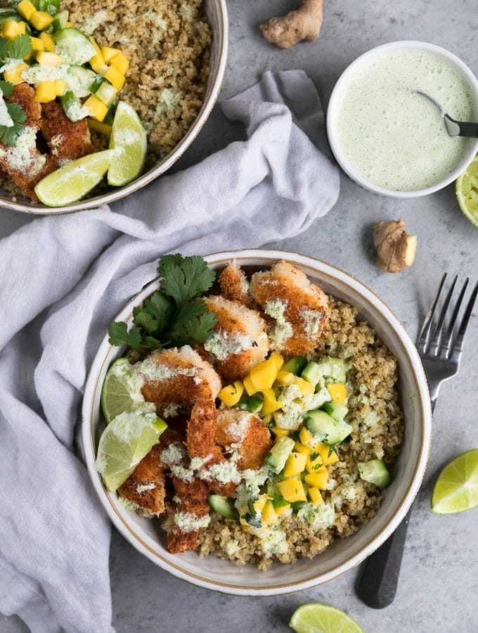 Overhead shot of two bowls filled with quinoa, coconut shrimp, mango salsa, lime, and cilantro