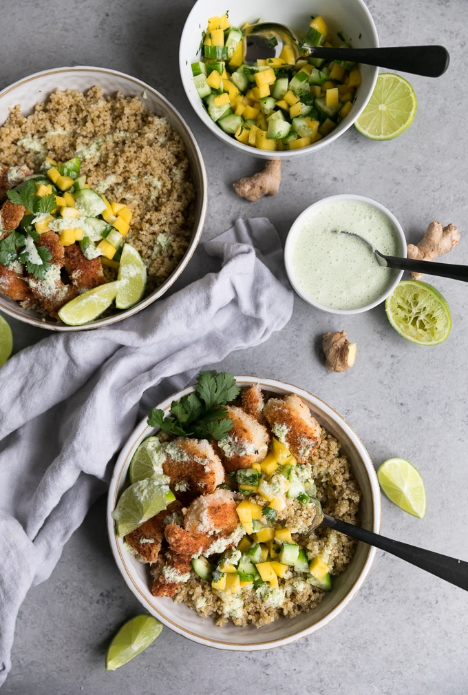 Overhead shot of two bowls filled with quinoa, coconut shrimp, mango salsa, lime, and cilantro with a bowl of lemongrass sauce off to the side with a spoon in it