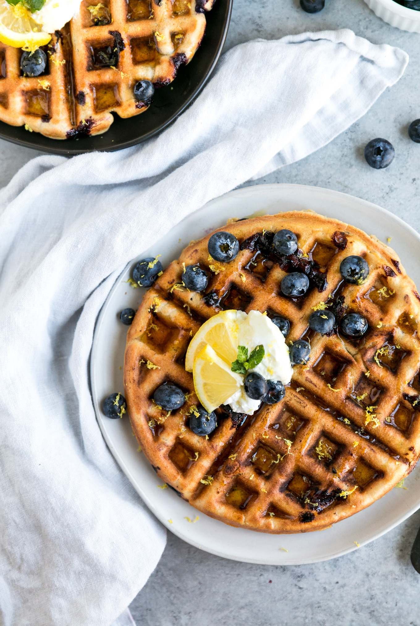 Overhead shot of a waffle topped with blueberries, greek yogurt, and lemon slices