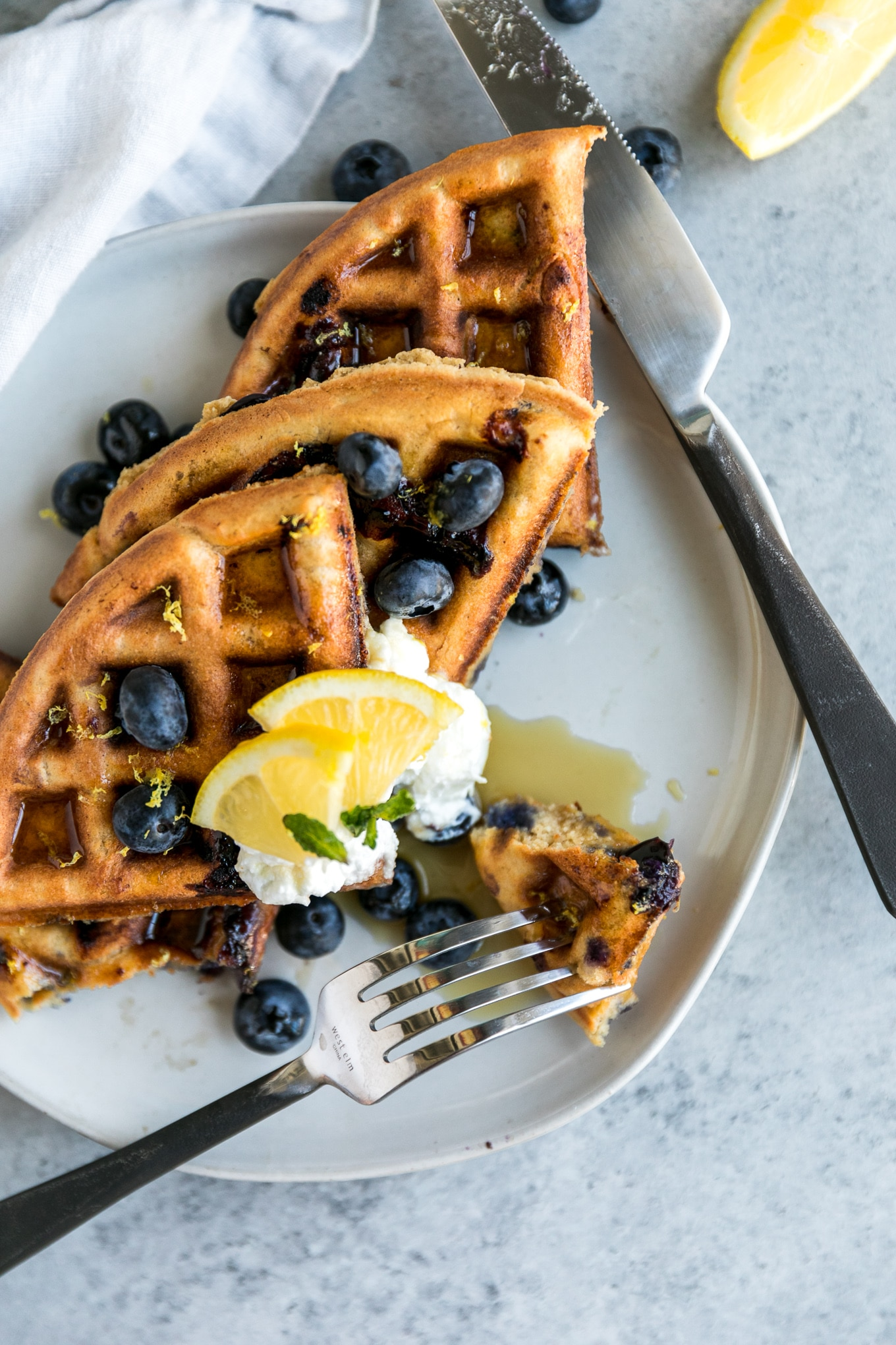 Overhead close up shot of a plate of waffles being cut into with a fork